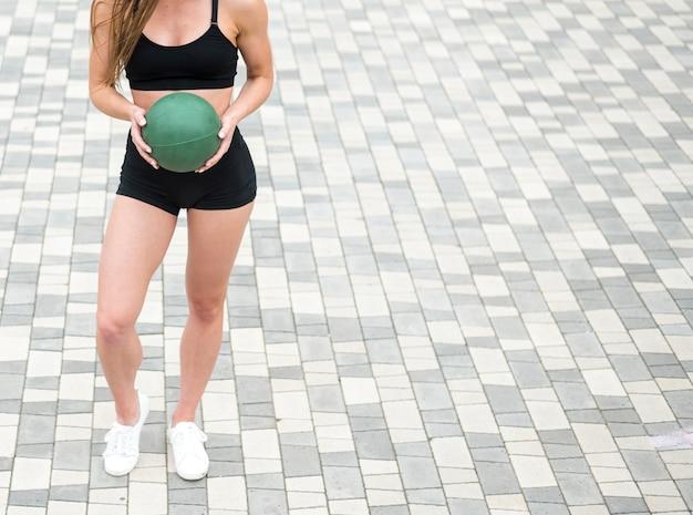 Sportliche frau, die eine hohe winkelsicht des eignungsballs hält