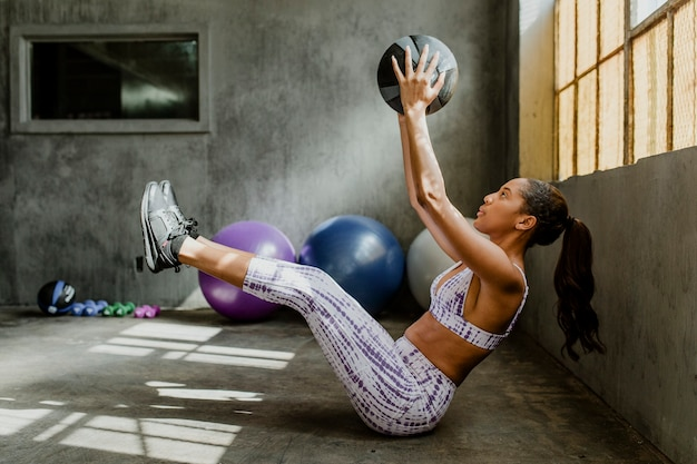 Sportliche frau, die einen fitnessball hält