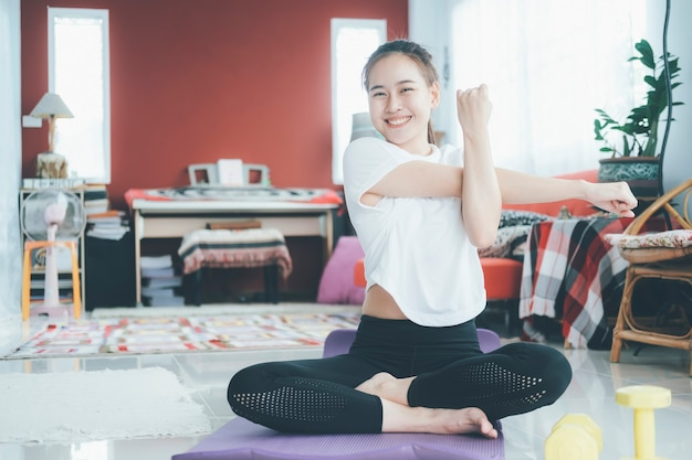 Sportliche frau, die fitness-streckübungen zu hause im wohnzimmer tut. bleiben sie zu hause und leben sie gesund.