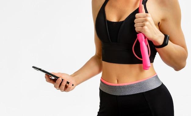 Sportliche frau, die fitness-tracker mit smartphone auf leerraum prüft. cardio-trainingskonzept.