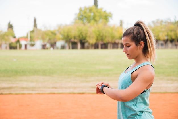 Sportliche frau, die fitnesstracker betrachtet