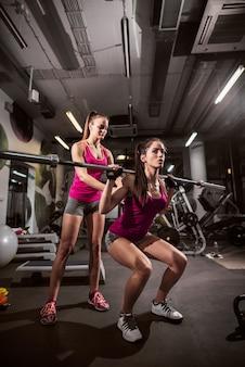 Sportliche frau, die gewichtsstange beim ausdauerheben anhebt. personal trainer hilft ihr.