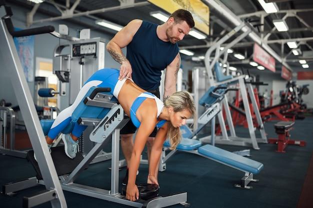 Sportliche frau, die gewichtsübungen mit hilfe ihres persönlichen trainers im fitnessstudio macht