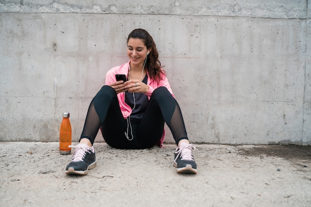 Sportliche frau, die ihr telefon benutzt.