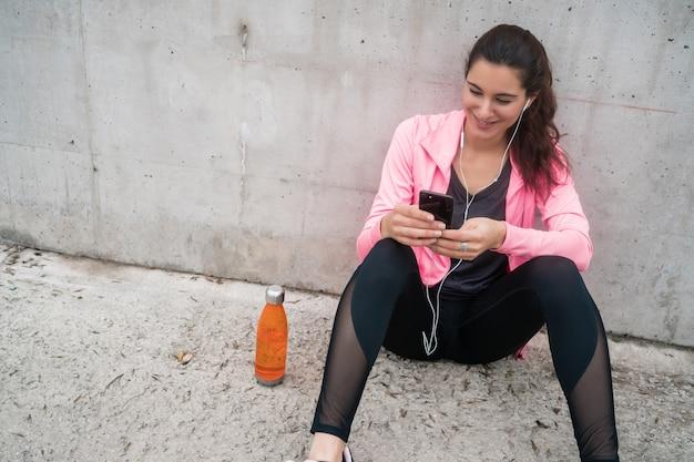 Sportliche frau, die ihr telefon benutzt
