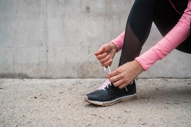 Sportliche frau, die ihre schnürsenkel bindet.