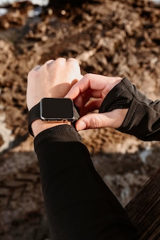 Sportliche frau, die ihre smartwatch repariert