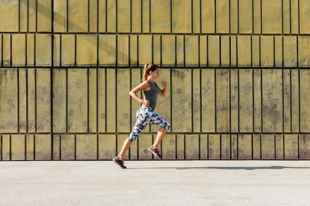 Sportliche frau, die in städtische umwelt läuft