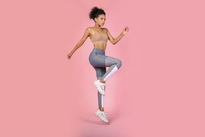 Sportliche frau, die kniebeugenübungen im studio übt. afrikanische frau in sportbekleidung, die auf rosa hintergrund arbeitet.