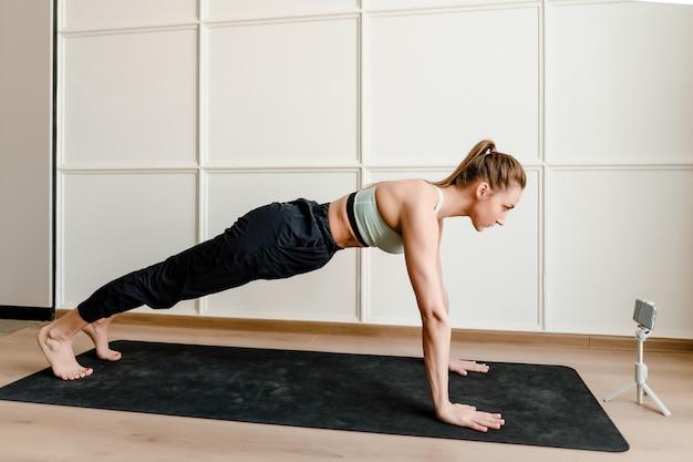 Sportliche frau, die körperliche übung zu hause auf yogamatte tut