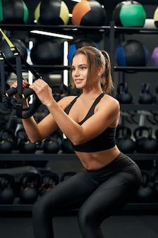 Sportliche frau, die lächelt und übung mit trx system tut