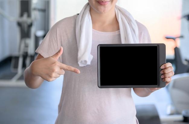 Sportliche frau, die leere tablette im fitness-studio hält. wellness und gesund mit technik.