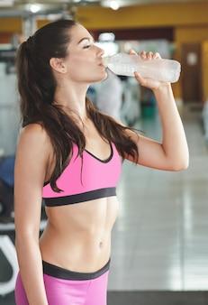 Sportliche frau, die mineralwasser nach dem training im fitnessstudio trinkt
