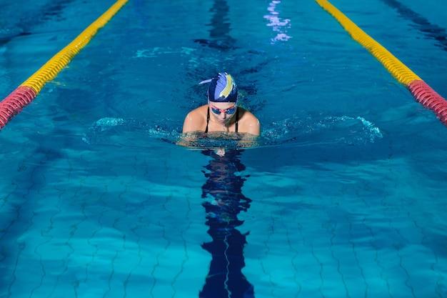 Sportliche frau, die mit schwimmhut und brille im schwimmbad schwimmt