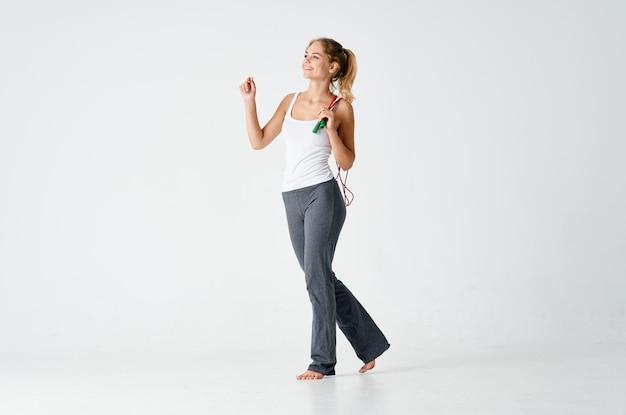 Sportliche frau, die mit springseilmotivation schlanke figur trainiert