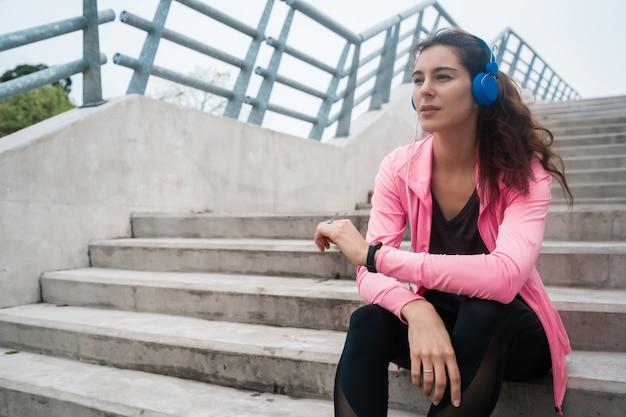 Sportliche frau, die musik auf einer pause vom training hört