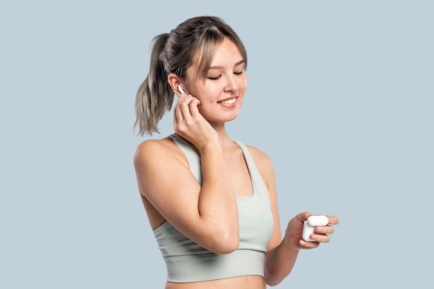 Sportliche frau, die musik über kopfhörer hört