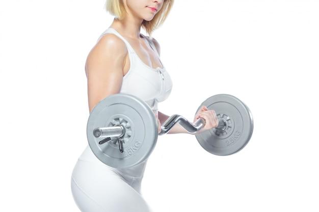 Sportliche frau, die muskeln mit langhantel auf weiß aufpumpt