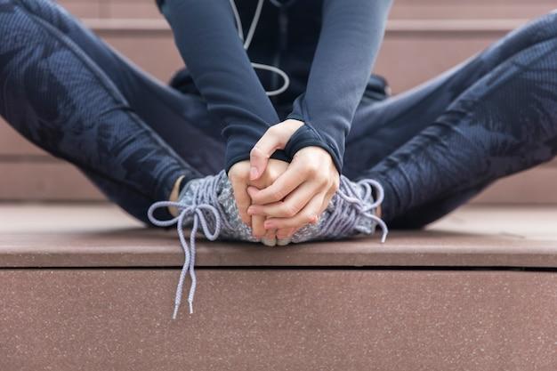 Sportliche frau, die nach training oder übung auf der treppe im freien sitzt und stillsteht