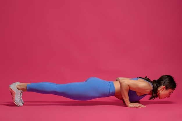 Sportliche frau, die niedrige plank-pose übt