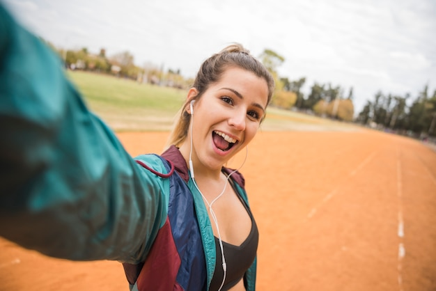 Sportliche frau, die selfie auf stadionsbahn nimmt
