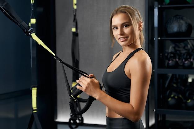 Sportliche frau, die sich auf training mit trx system vorbereitet