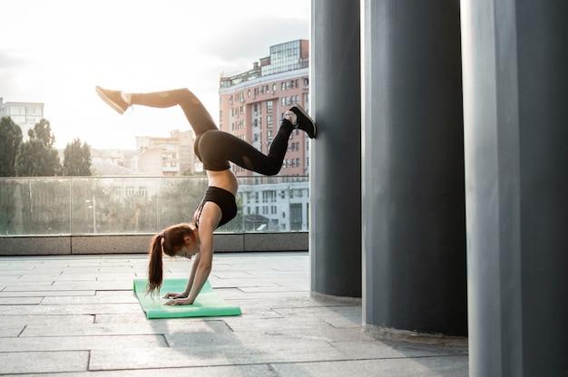 Sportliche frau, die sich mit leichtathletik beschäftigt, sie trainiert morgens auf der straße, die frau macht den trick an ihren händen auf dem spielplatz