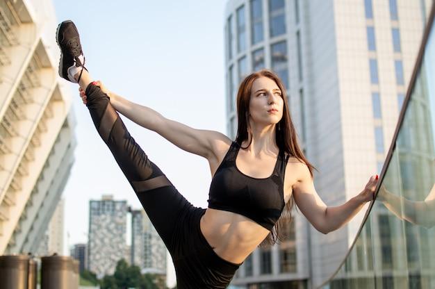 Sportliche frau, die sich mit leichtathletik beschäftigt, sie trainiert morgens auf der straße, eine frau macht stretching- und gymnastik-tricks