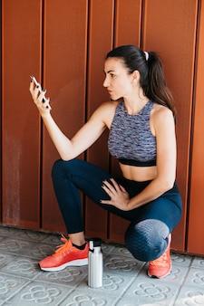 Sportliche frau, die smartphone betrachtet