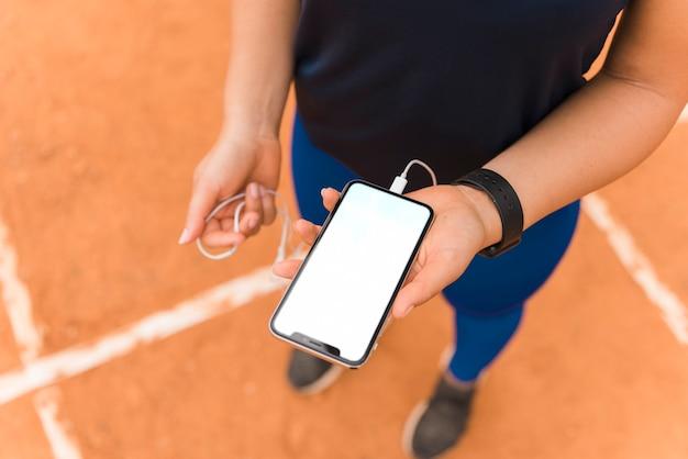 Sportliche frau, die smartphoneschablone darstellt