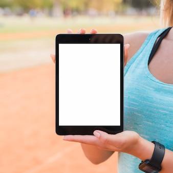 Sportliche frau, die tablettenschablone darstellt