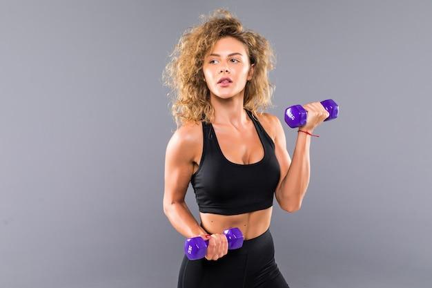 Sportliche frau, die übung für arme tut. foto des muskulösen fitnessmodells, das mit hanteln auf grauer wand arbeitet. kraft und motivation