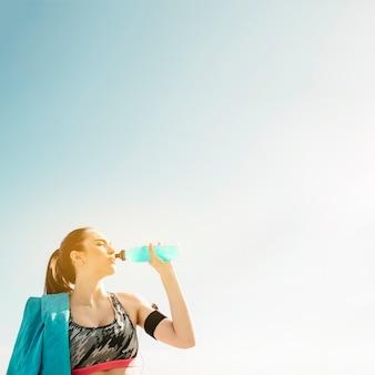 Sportliche frau, die von der flasche auf himmelhintergrund trinkt
