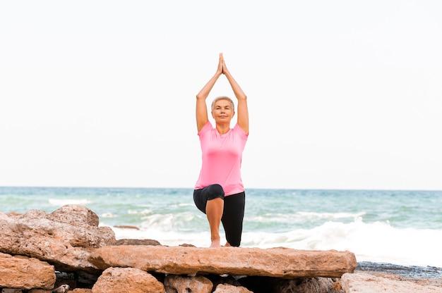 Sportliche frau, die yoga am strand praktiziert, das dehnen tut und gleichgewicht ausübt.