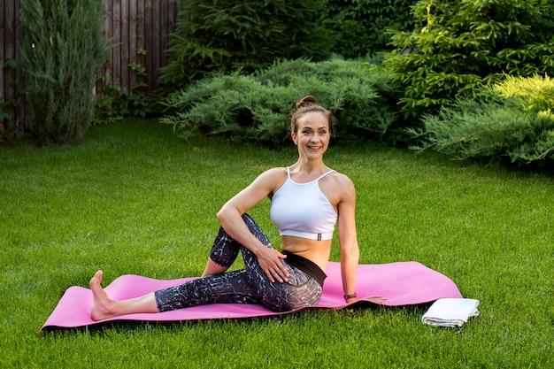 Sportliche frau, die yoga praktiziert und drehungen für die rückenmuskeln macht. sie lacht