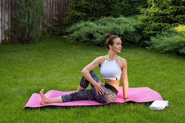 Sportliche frau, die yoga praktiziert und drehungen für die rückenmuskeln macht.