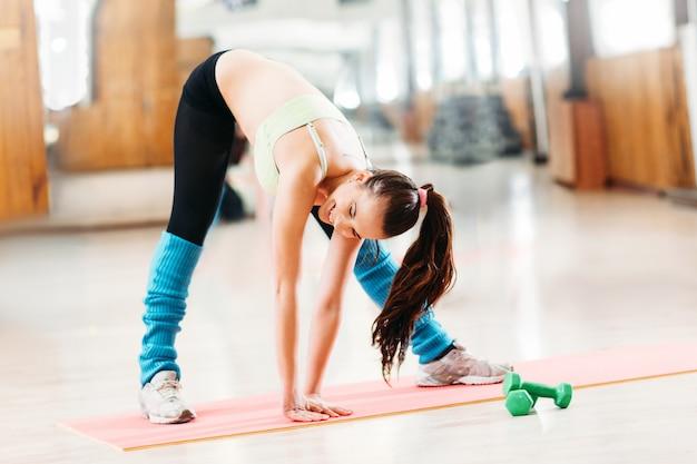 Sportliche frau, die zehen berührt und im fitnessstudio streckt