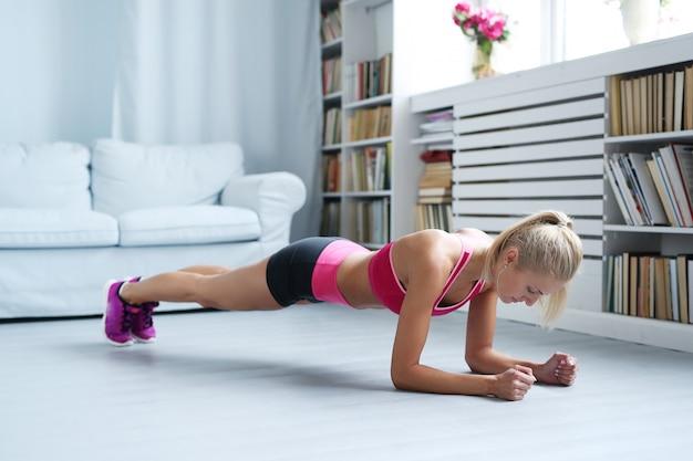 Sportliche frau, die zu hause trainiert, training