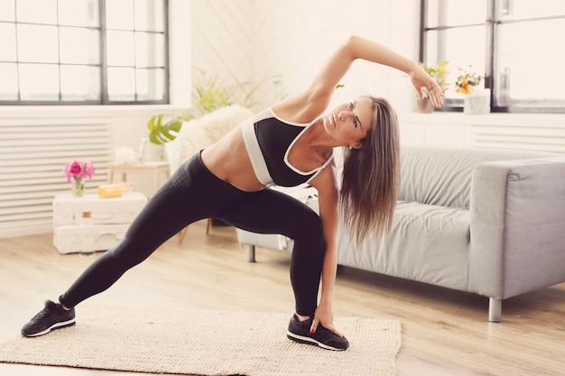 Sportliche frau, die zu hause trainiert