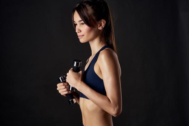 Sportliche frau fitness hanteln in den händen von starkem isoliertem hintergrund