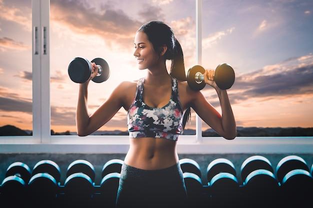 Sportliche frau hält fitness-hantel mit einem lächeln, das mit sonnenuntergangwolkenhimmel im hintergrund trainiert