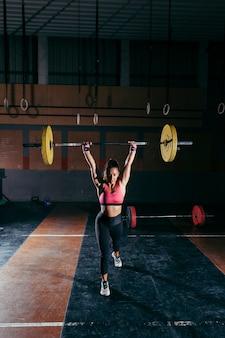 Sportliche frau hebt hantel im fitnessstudio an