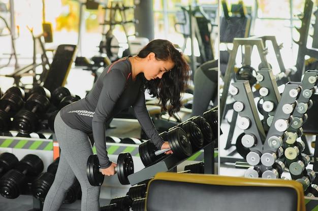 Sportliche frau im fitnessstudio. frau, die gewichte hebt und an ihrer brust im fitnessstudio arbeitet