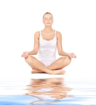 Sportliche frau in baumwoll-unterwäsche, die yoga-lotus-pose auf weißem sand praktiziert