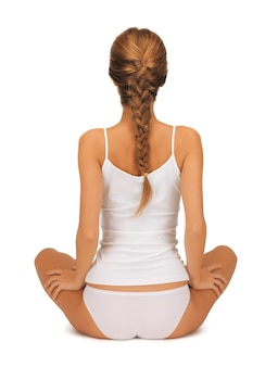 Sportliche frau in baumwoll-unterwäsche, die yoga-lotus-pose praktiziert