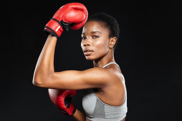 Sportliche frau in boxhandschuhen mit blick nach vorne über graue wand