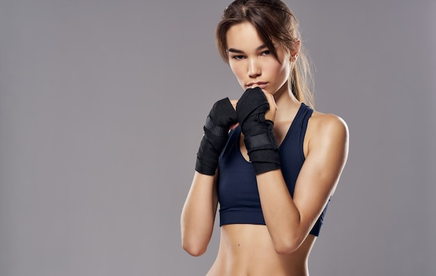 Sportliche frau in den boxhandschuhen auf grauem hintergrund kopieren raum. hochwertiges foto