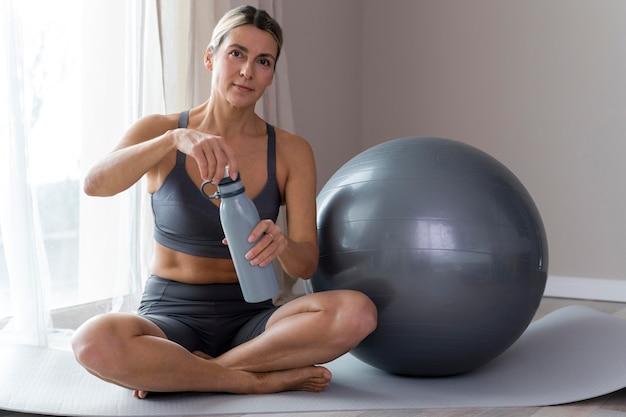 Sportliche frau in der blauen fitnesskleidung, die eine flasche öffnet