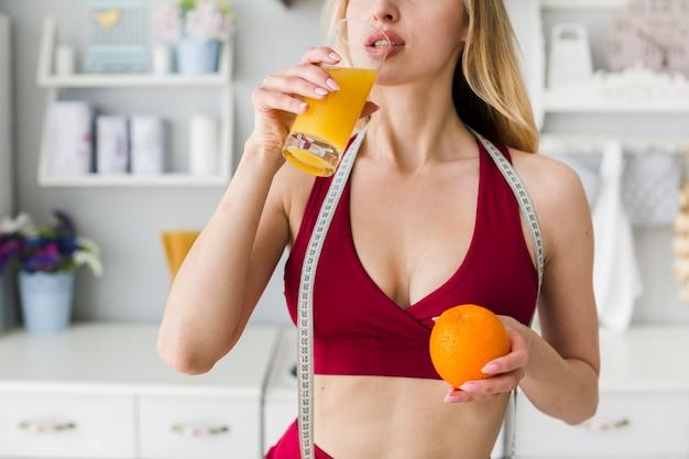 Sportliche frau in der küche mit gesundem saft