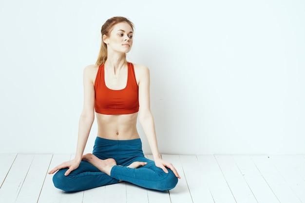 Sportliche frau in der pose auf dem boden zu hause